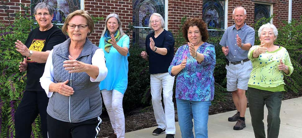 A group of elders are seen practicing Tai Chi outside in front of a senior center.