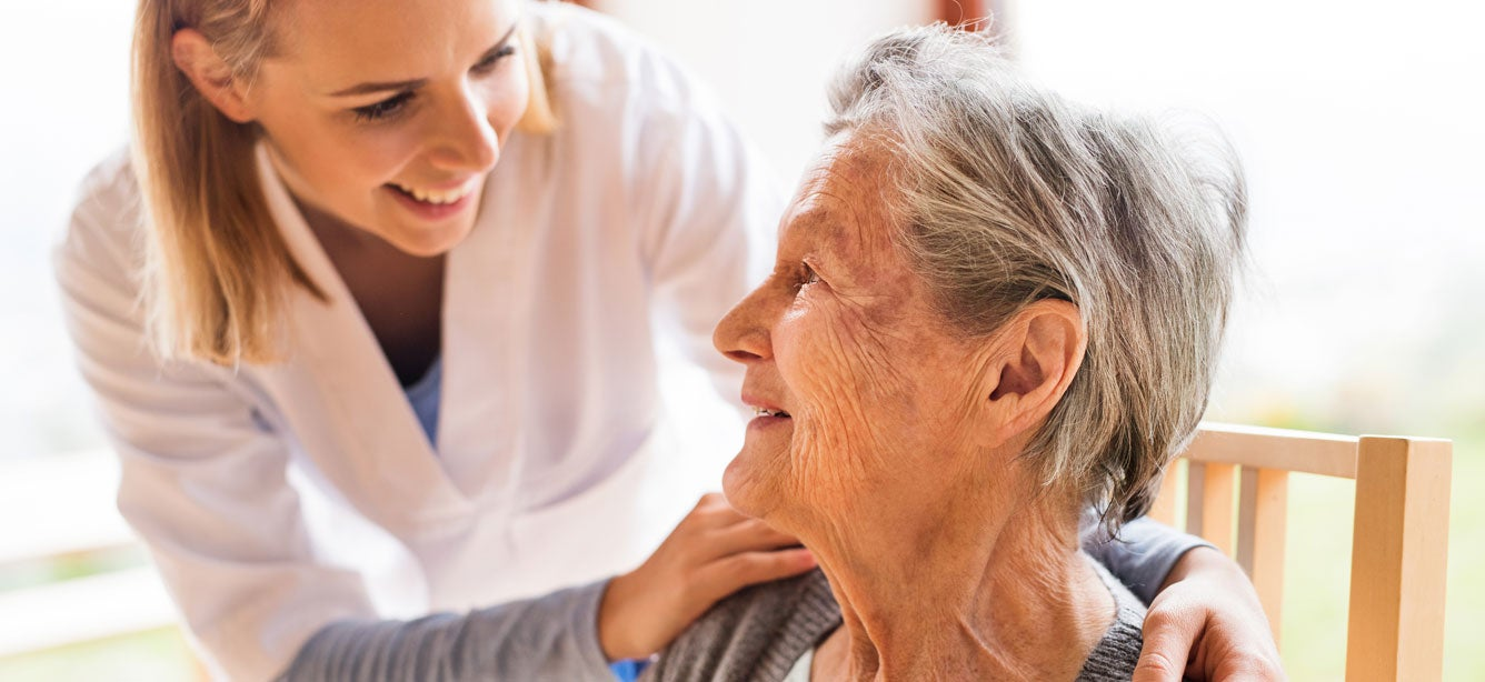 A young health care worker is providing support to a senior woman during a home visit.