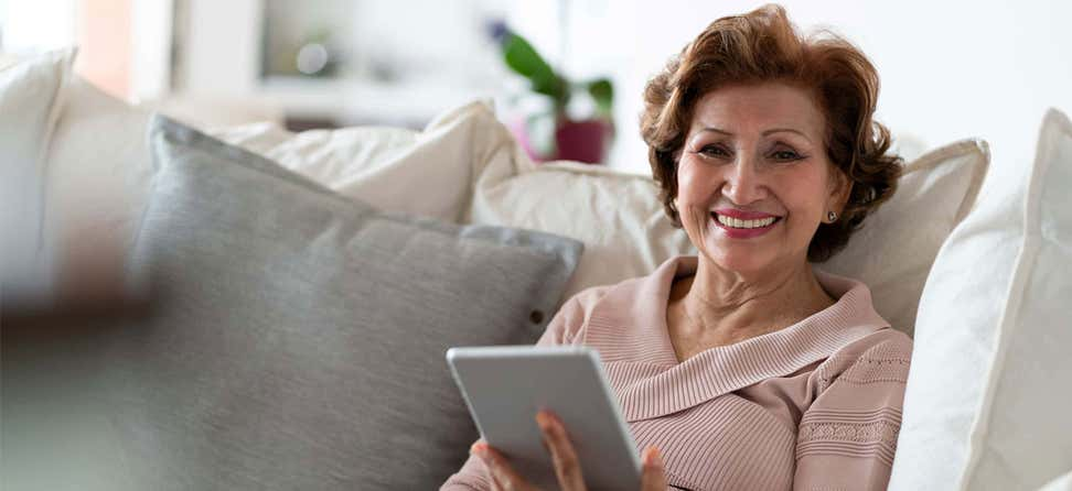 Older Hispanic/Latina woman on couch with tablet.