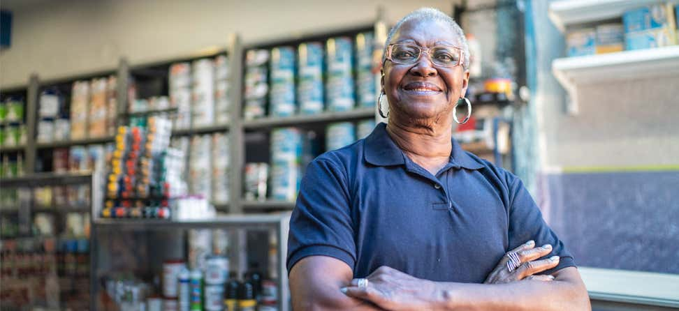 A Black, working senior woman stands with her arms crossed in front of a paint store.