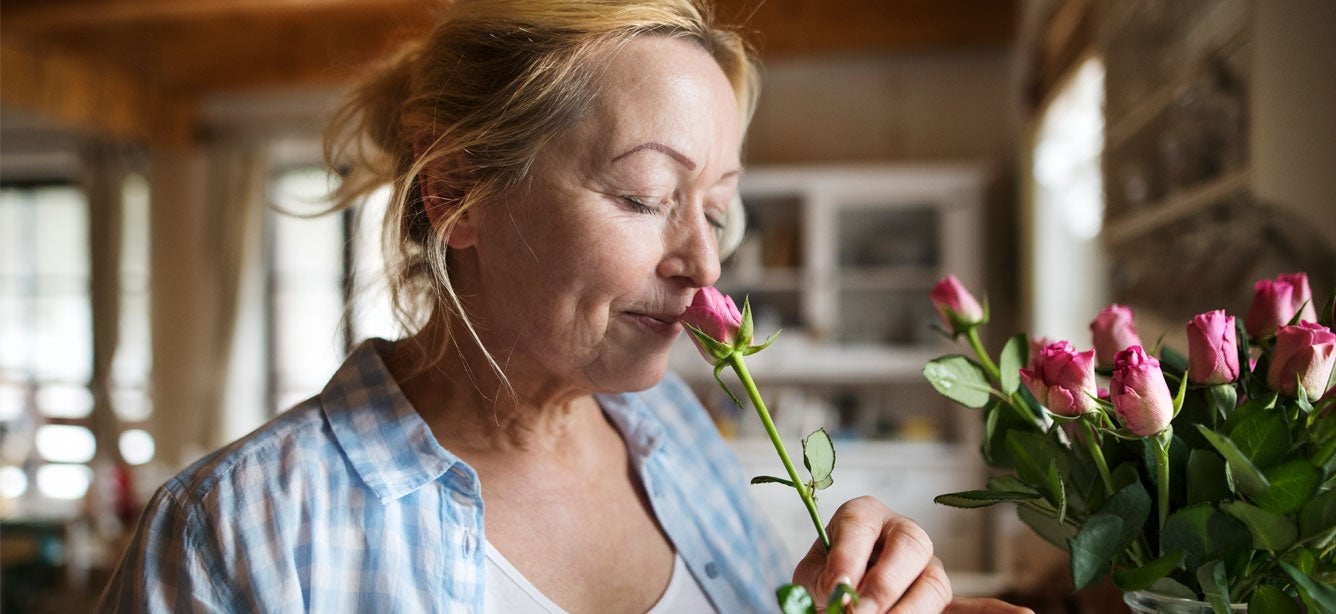 An older Caucasian woman is taking time to sleep the roses in her kitchen.