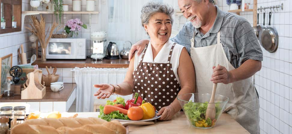 A senior Asian couple are embracing while preparing a healthy meal in their kitchen.