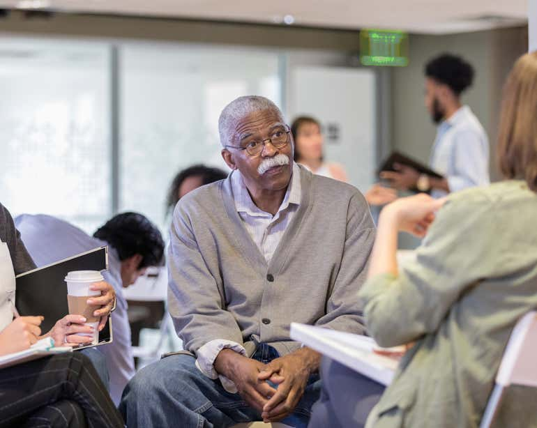 A Black senior man is sitting in a group having a discussion with other older adults.