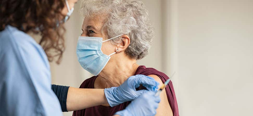 doctor gives a vaccine injection to senior woman at the hospital
