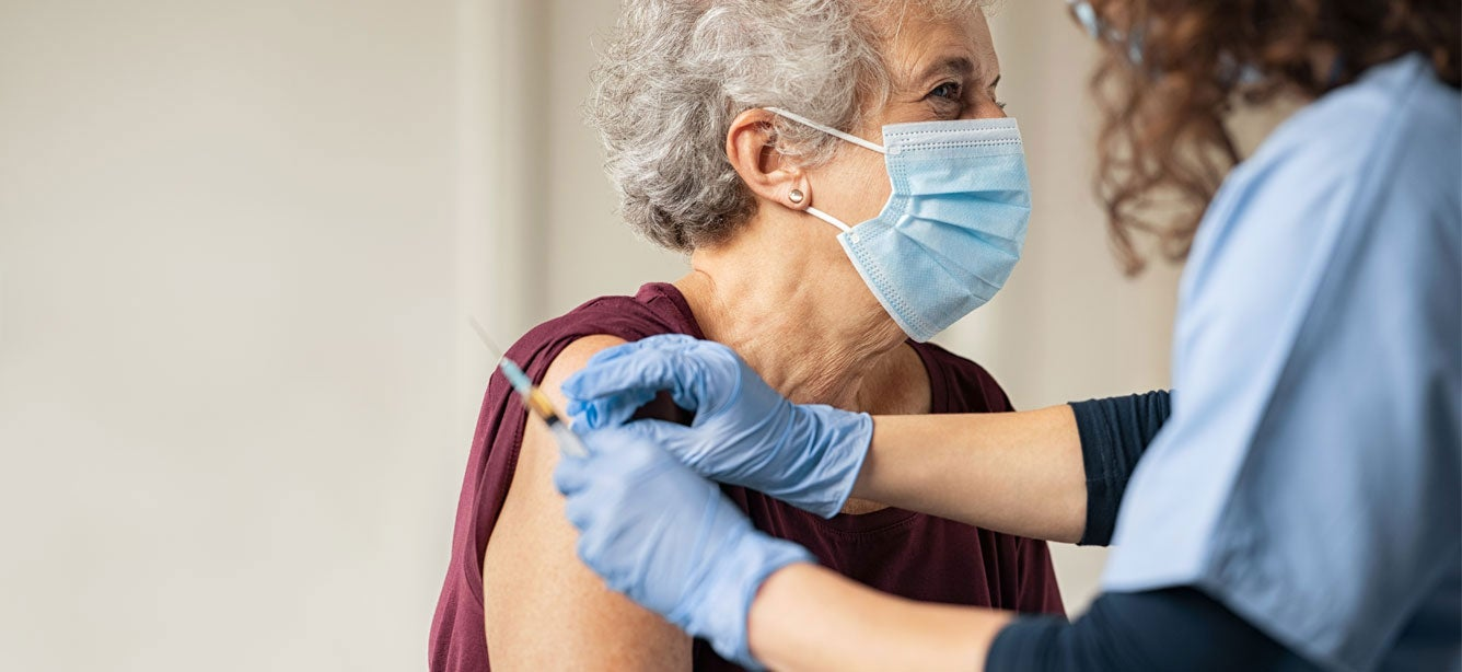 senior white woman with mask receiving covid vaccine