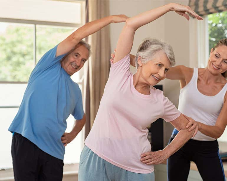 A young female trainer is helping a senior Caucasian couple with stretching exercises at home.