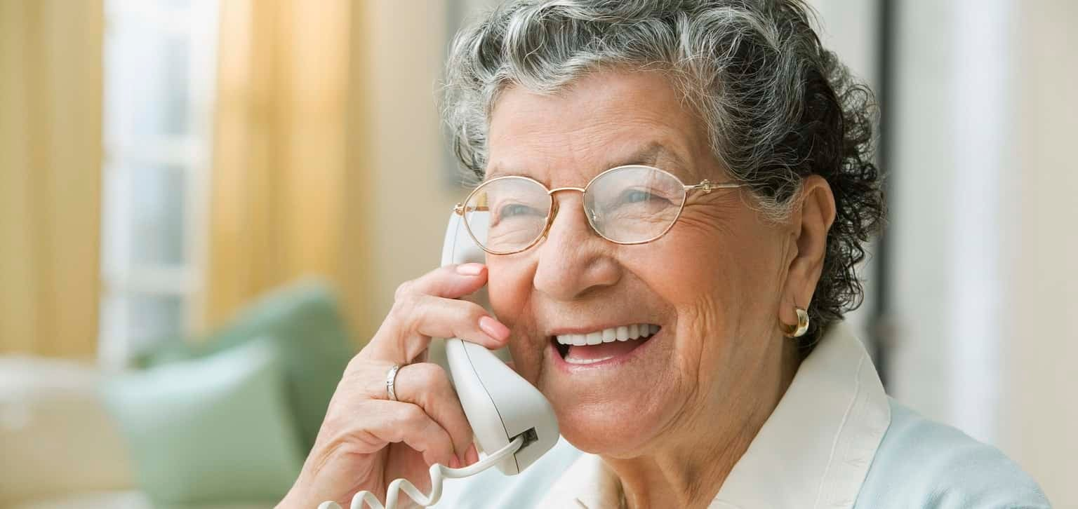 An older woman is talking on her landline, smiling and looking off camera.
