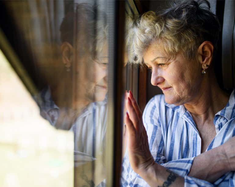A sad, Caucasian senior woman stares out her window.