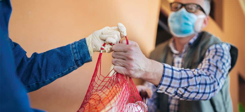A senior male wearing a mask is receiving a grocery delivery from a caregiver wearing gloves during the pandemic.