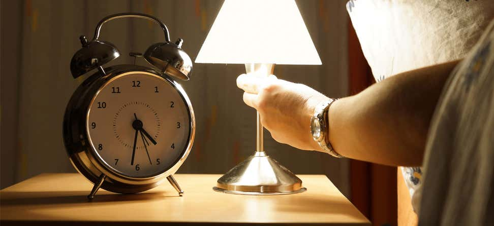 A senior woman in bed is turning off her lamp, indicating that she's going to sleep.
