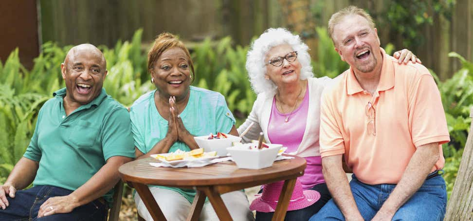 Two senior couples are outside enjoying a meal together, laughing and having a good time.