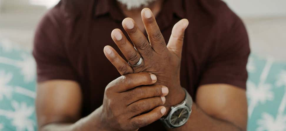 Cropped shot of a Black man sitting down, suffering from arthritis in his hand.