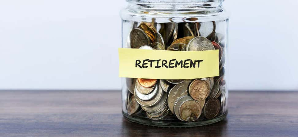 """A jar filled with various coins has a sticky note with the words """"Retirement"""" on it."""
