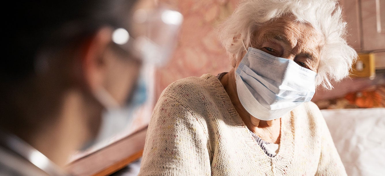 senior masked woman talking with her healthcare provider at home