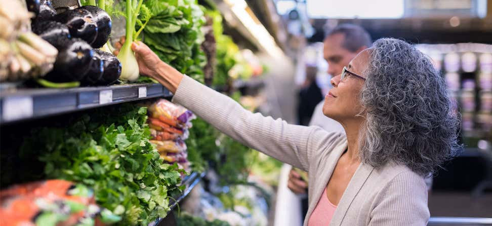 A Black woman is shopping for produce in the grocery store.