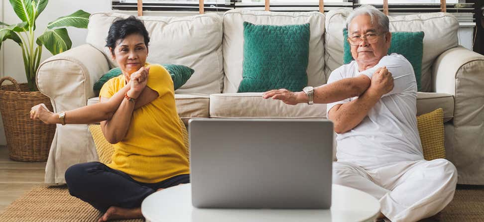 A senior Asian couple are practicing yoga in their living room virtually.