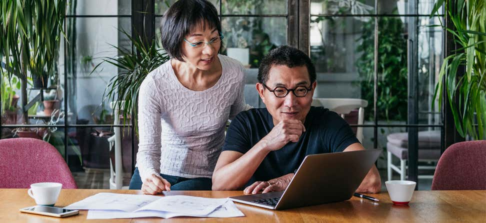 An older Asian couple is contemplating financial decisions over coffee.