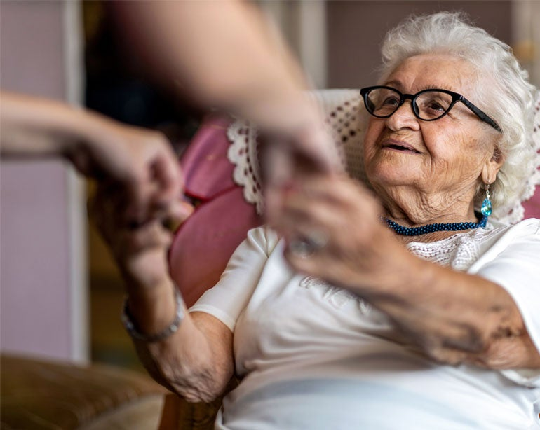 A senior woman is provided help to stand to help her prevent from falling.