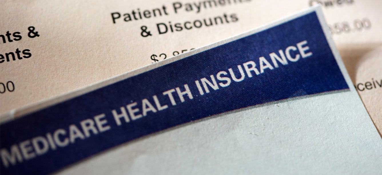 Closeup shot of a hospital bill alongside a Medicare enrollment form.