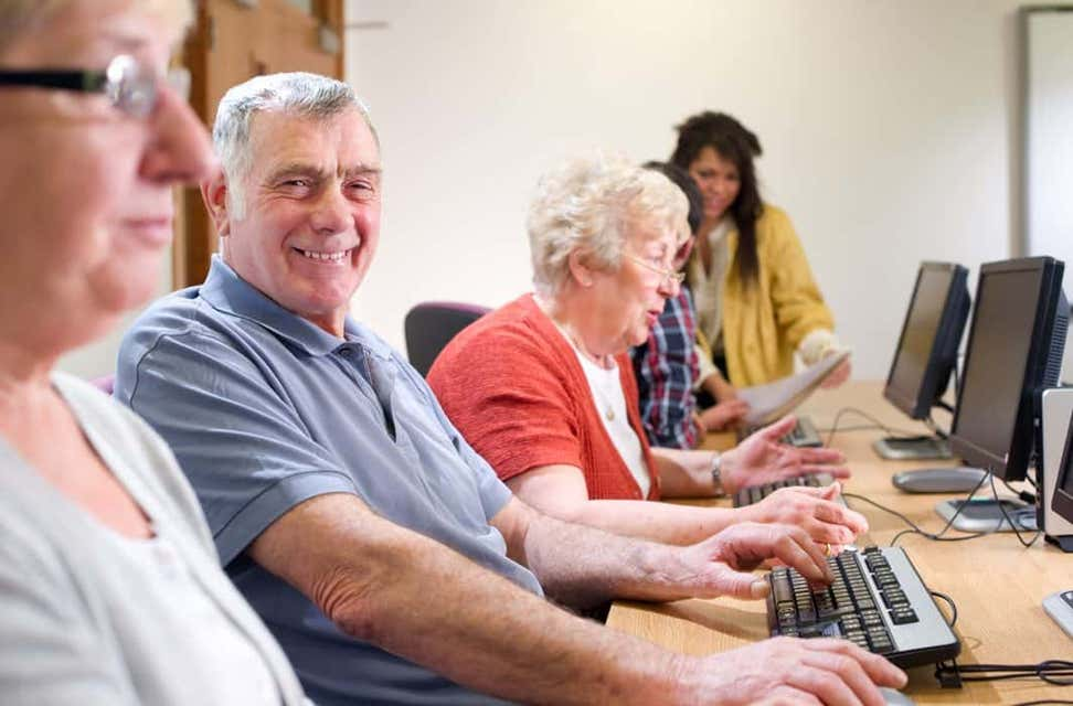 A group of seniors are smiling on a job training site while doing work on computers.
