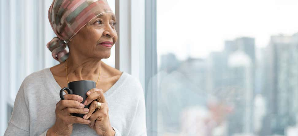 A black senior woman with cancer is wearing a scarf on her head, staring out the window of her hospital room.