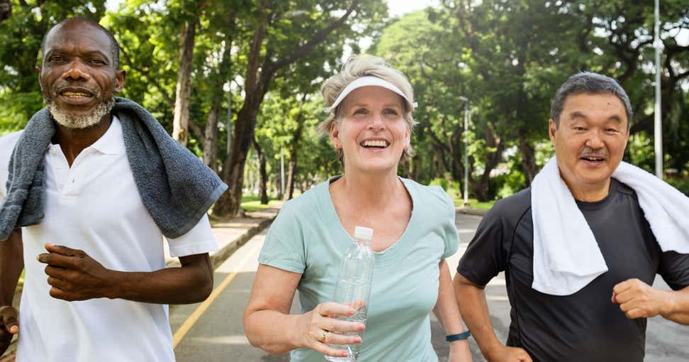 A group of older adults are running in the street for exercise, the senior woman carrying a water bottle.