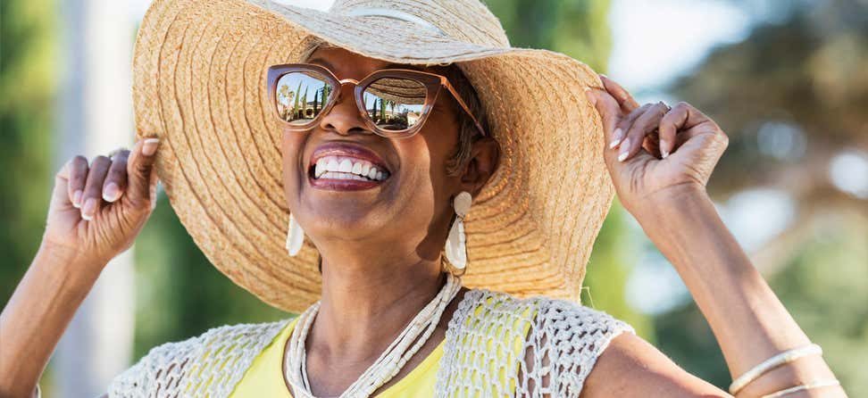 A Black senior woman is radiant in the sun, wearing sunglasses and a brimmed hat while smiling.