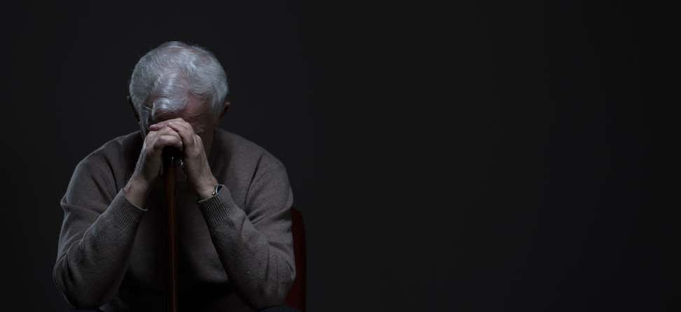 A Caucasian senior man is sitting in the dark with his head bent over on his cane, seemingly depressed.