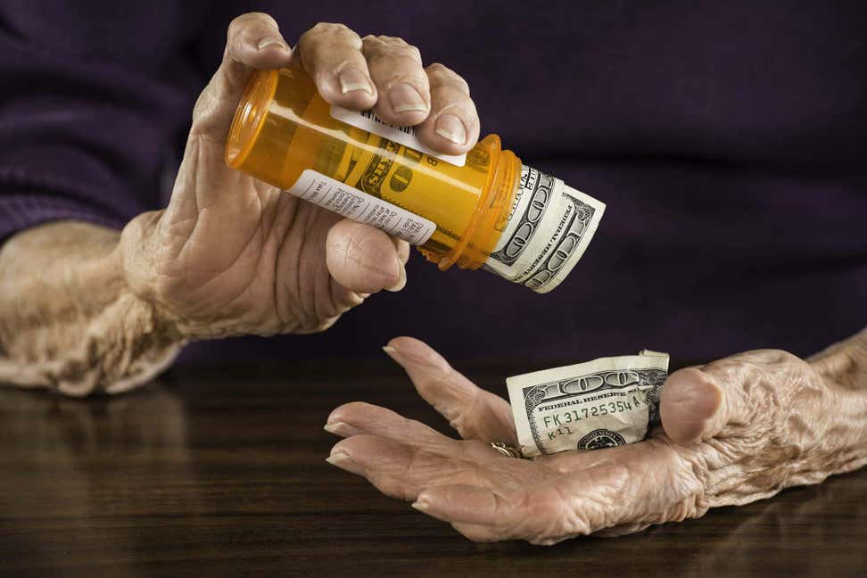 Older woman's hands shaking out $100 bills from prescription medicine bottle.