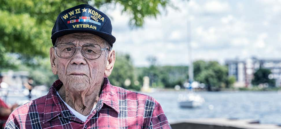 A close up shot of a senior male Veteran looking straight at the camera with the beach/harbor in the background.