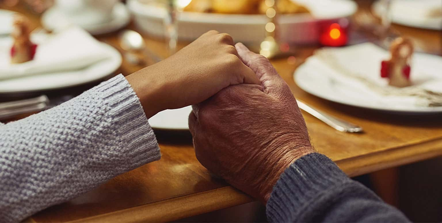 A male senior is holding a young girl's hand while sitting at holiday dinner table.