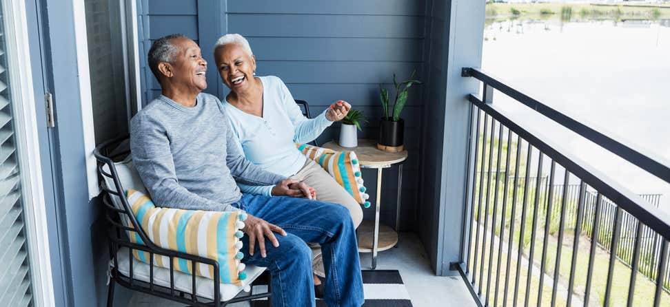 A senior Black couple is laughing and enjoying their time together on their porch.