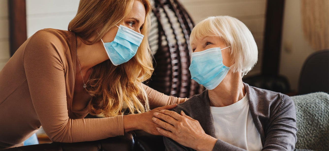 A senior woman is being looked after by her caring daughter at home, both of which are wearing masks.