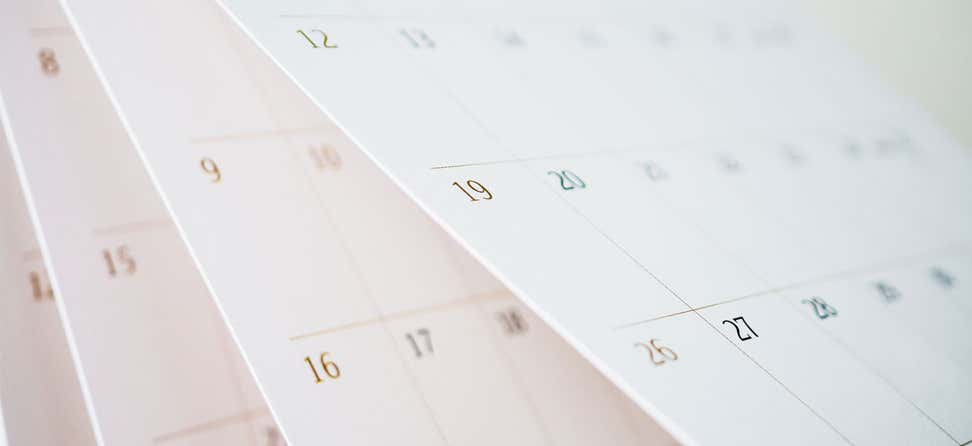 A closeup shot of the pages of a calendar turning, indicating time passing.