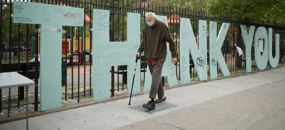 senior man wearing a face mask walks by a sign supporting health care workers