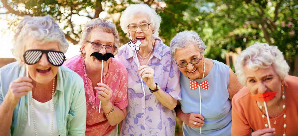 A group of senior women are having fun, holding up mustache/various masks while posing for a photo together.