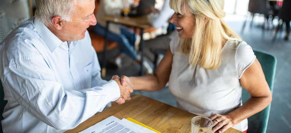 A senior Caucasian female shakes hands with a senior Caucasian man. Both are sitting at a table, discussing a financial agreement.