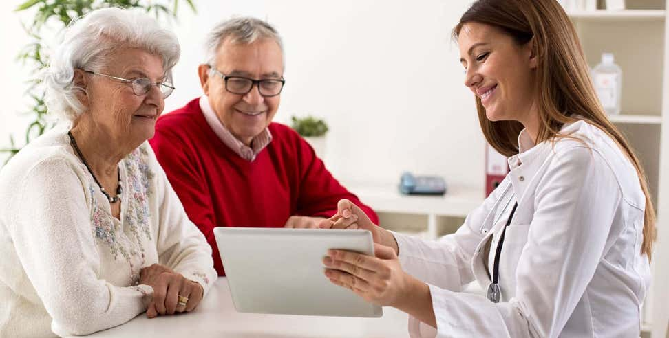 Older Caucasian couple reviewing medical information with doctor on a tablet