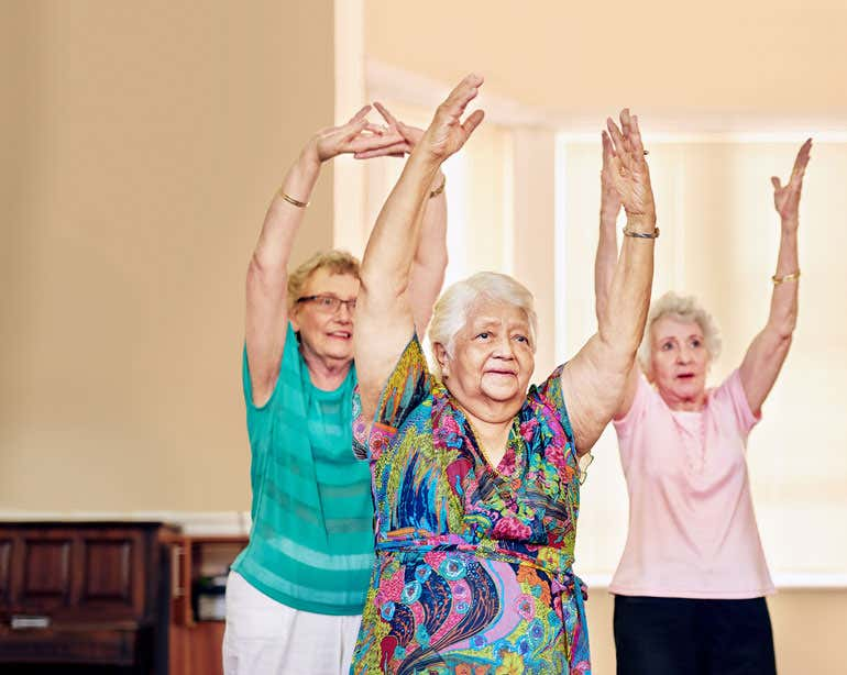 Three senior women are exercising indoors together.