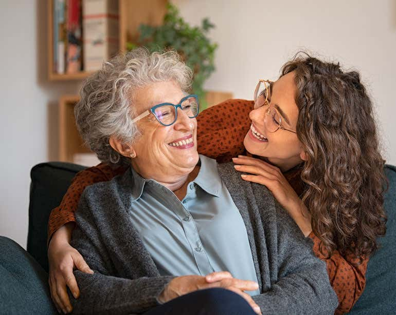 A senior woman wearing glasses is smiling while being hugged by her younger female caregiver, that's also wearing glasses.