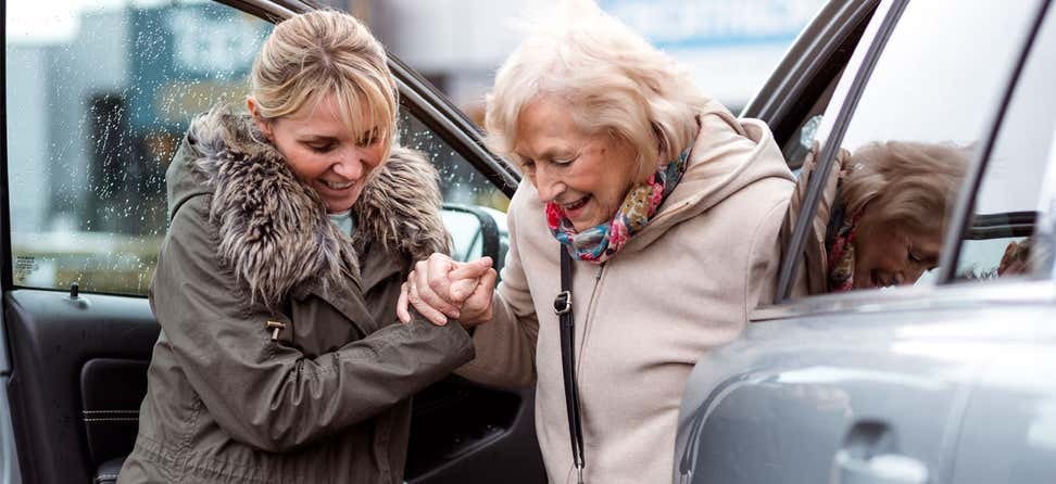 A young female caregiver helps a senior woman out of the passenger seat of her car.