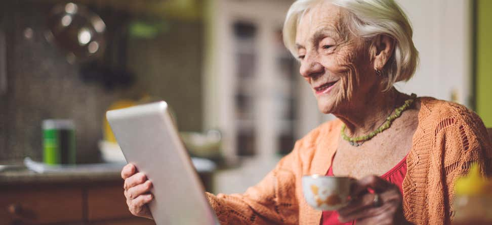 A senior woman uses her tablet to calculate her finances while drinking hot tea.