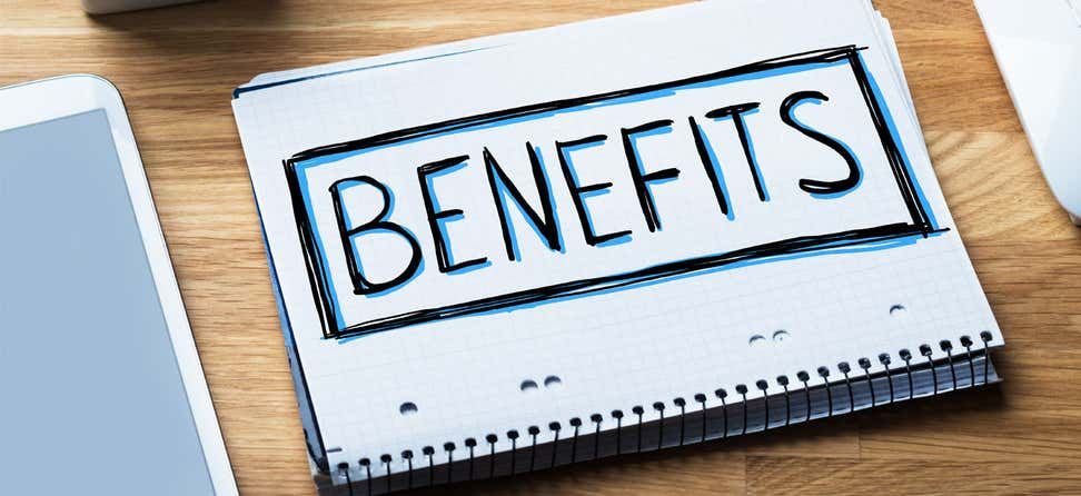 "The word ""Benefits"" written on a notebook that's on an office table."