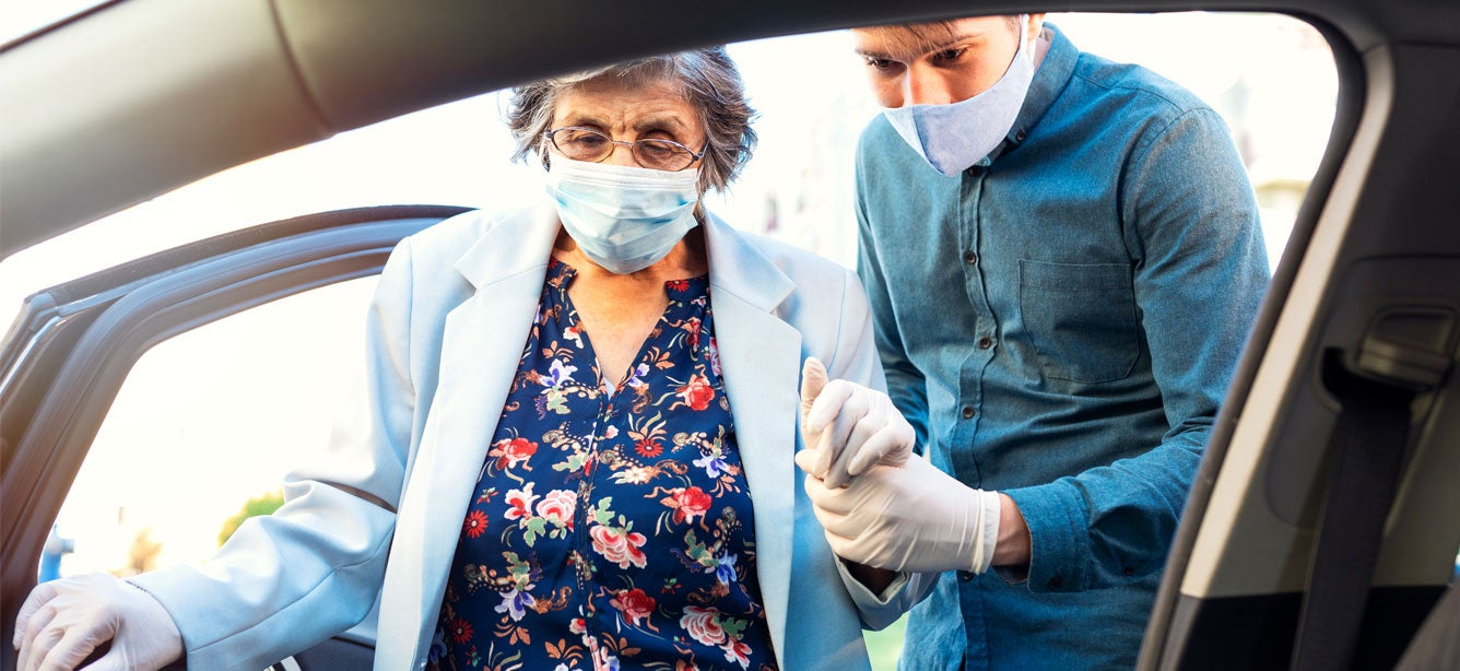 A young male masked caregiver is helping a masked senior woman into the car.