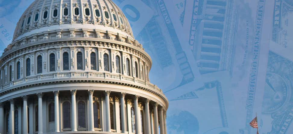A shot of the U.S. Capitol dome overlaid on top of a background of one-hundred dollar bills.