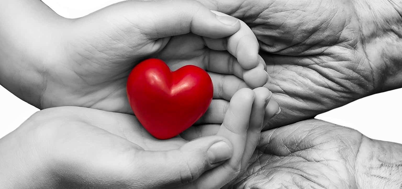 An elderly woman and her granddaughter hold a heart in their hands.