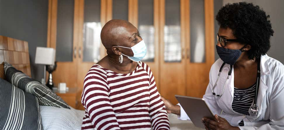 A Black senior woman wearing a mask is talking to her health care provider at home.