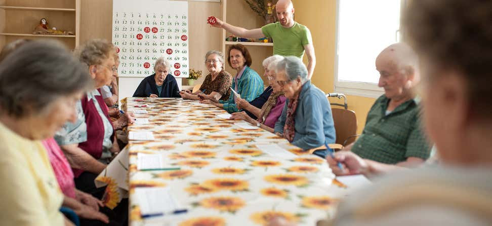 A group of older adult women are playing Bingo in a senior center during the day.