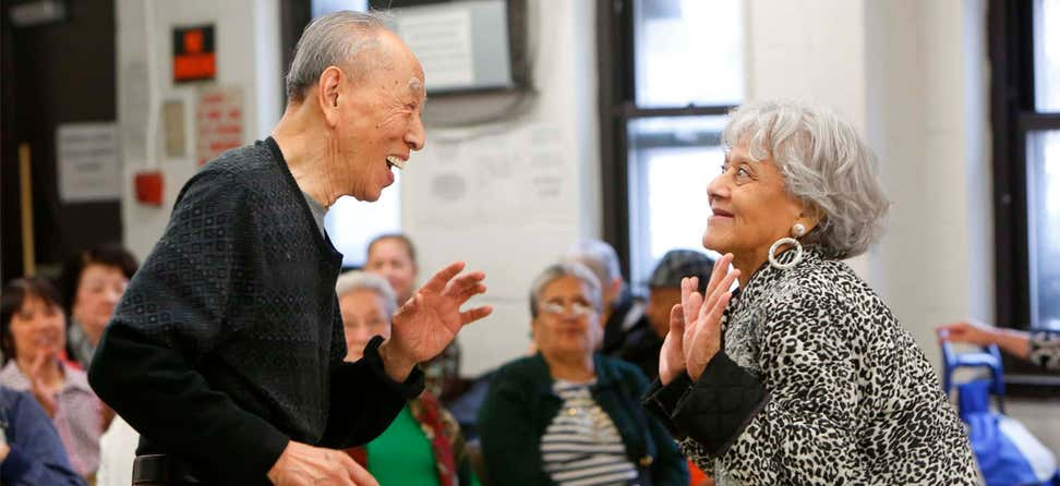 Two older adults are dancing together in front of a group at a local senior center.