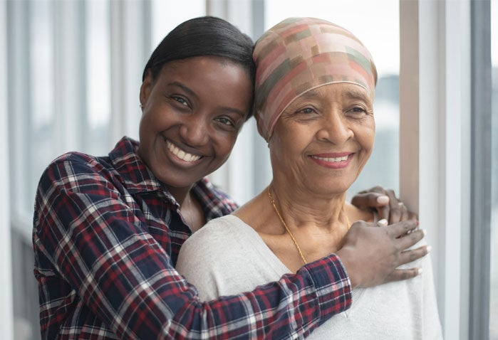 A Black senior woman is being hugged by her caregiver, daughter.